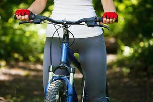 Primer plano de las manos en guantes protectores rojos con manillar. foto