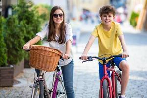 Ciclismo urbano- niña y niño en bicicleta en la ciudad foto