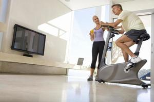 woman smiling at man riding stationary bicycle in living room