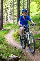 menina andando de bicicleta em trilhas da floresta