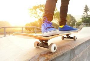 piernas en zapatillas de deporte en una patineta