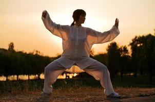 mujer en traje blanco hace ejercicio taiji chuan 3 foto