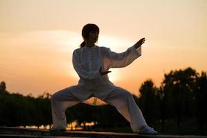 mujer en traje blanco hace ejercicio de taiji chuan - 4 foto