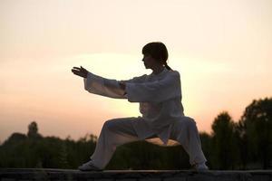 mujer en traje blanco hace ejercicio de taiji chuan foto