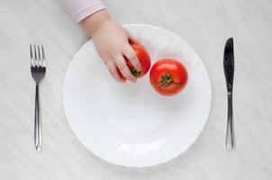 Tomato in hand photo