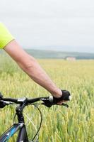 Man holding a bike in cereal field