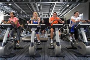homens e mulheres andando de bicicleta ergométrica no health club