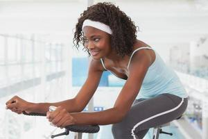 Fit woman working out on the exercise bike photo