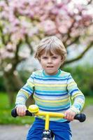 niño pequeño niño montando con su primera bicicleta