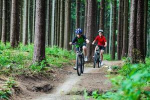 Teenage girl and boy biking on forest trails photo