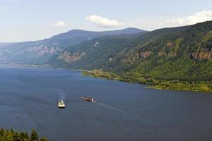 Two barges on the Columbia River with the hilly banks