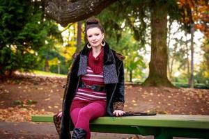 Fashionable young woman in park photo