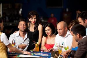 hombres jóvenes y hombres jugando al blackjack foto