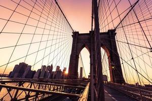 puesta de sol del puente de brooklyn con manhattan skyline us foto