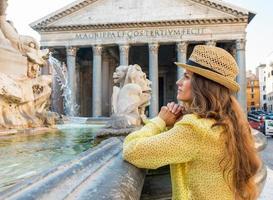 Mujer pensativa cerca de la fuente del panteón en Roma, Italia foto