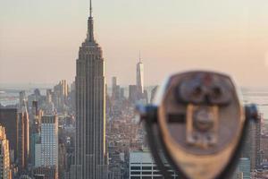 binoculares con rascacielos de nueva york en el fondo al atardecer