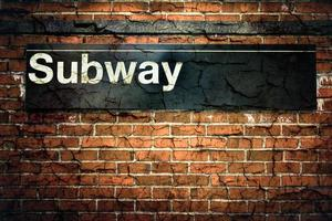 A cracked and unfortunate subway sign hanging on a wall
