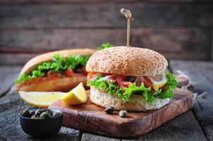 burger with pickled salmon, lettuce, white onion and capers