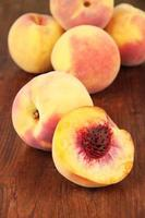 Ripe sweet peaches, on wooden background
