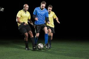 Soccer players tackling on pitch