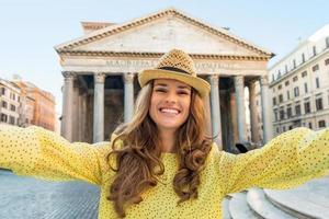 Mujer joven feliz haciendo selfie cerca del panteón en Roma, Italia foto