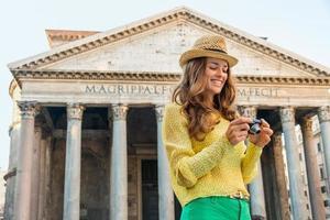 Mujer sonriente revisando fotos en el panteón en Roma