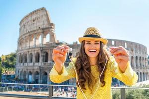 Woman giving headphones with audio guide near colosseum in rome