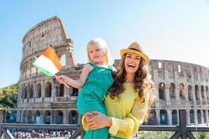 Madre sonriente con hija con bandera italiana y coliseo