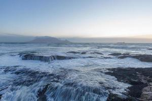 Waves breaking over rocks photo