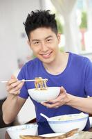 Young Chinese Man Sitting At Home Eating Meal photo
