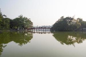 Rayo de sol Huc puente rojo en el lago Hoan Kiem, Hanoi, Vietnam