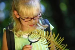 Young girl looking at fern with magnifying glass