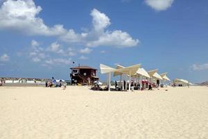 People on the sand beach in Herzliya Pituah, Israel.