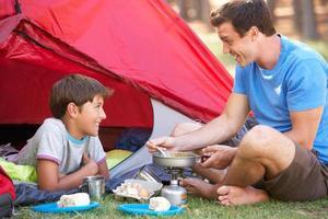 padre e figlio cucinano la colazione in vacanza in campeggio