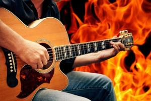 man playing guitar against fire