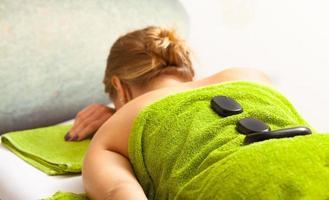 Salón de spa. Mujer relajante con masaje con piedras calientes. cuidado del cuerpo. foto