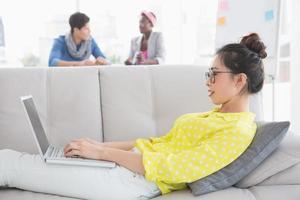 joven creativa usando laptop en sofá
