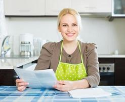 Woman with documents at kitchen photo