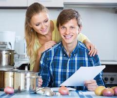 spouses signing documents and smiling at kitchen