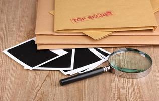 sobres con sello de alto secreto con papeles fotográficos en la mesa