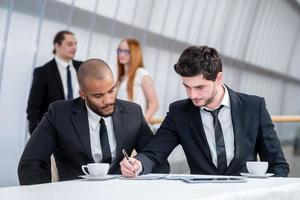 zakenman ondertekent documenten. twee succesvolle zakenlieden glimlachen
