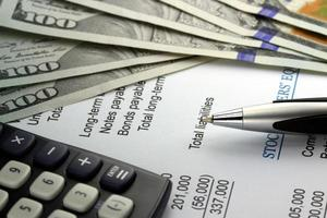 nosotros moneda, calculadora y documentos financieros closeup foto