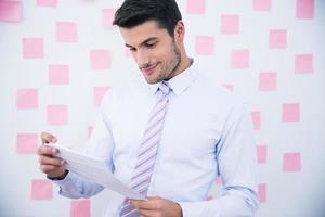 Happy businessman reading document photo