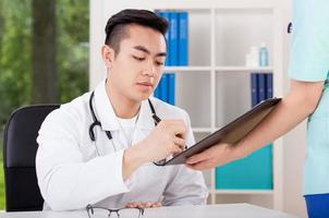 Asian doctor signing document photo