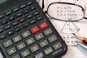 Brille, Stift und Bleistift über der Formel mit Taschenrechner