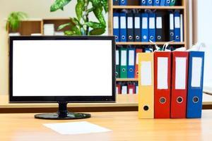 pantalla de monitor aislada y carpetas de colores para papeles en la mesa