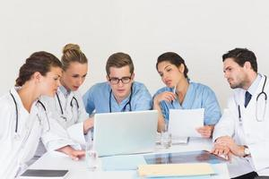 Doctors and nurses discussing information over a laptop photo