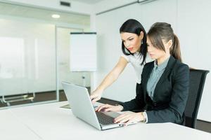 empresarias discutiendo logros mientras mira la computadora portátil foto