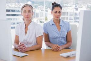 mujeres empresarias serias sentadas juntas foto