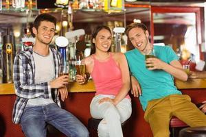 amis souriants, boire de la bière ensemble